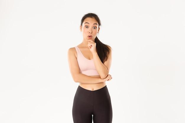 Przemyślana szczupła i wysportowana azjatycka dziewczyna fitness zbierająca siłownię, myśląca lub podejmująca decyzję, wyglądająca na rozbawioną i zdumioną do kamery, stojąca w odzieży sportowej.