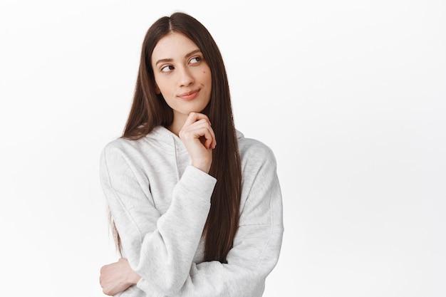 Przemyślana urocza dziewczyna z długimi włosami, patrząca na bok i uśmiechnięta podczas myślenia, stojąca zamyślona, dokonująca wyboru, wyobraź sobie coś ciekawego, białą ścianę
