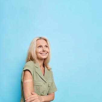 Przemyślana, zadowolona, ładna blondynka w średnim wieku nosi samoprzylepny bandaż na ramieniu, szczęśliwa po wykonaniu szczepień skoncentrowanych na pozycjach na tle niebieskiej ściany