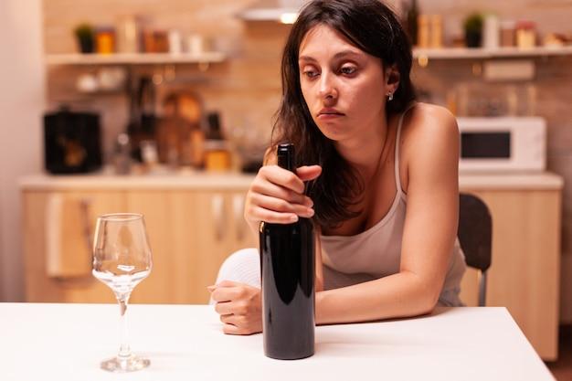 Przemyślana żona patrząc na kieliszek wina, siedząc na krześle. nieszczęśliwa osoba cierpiąca na migrenę, depresję, chorobę i stany lękowe, uczucie wyczerpania, zawroty głowy, objawy alkoholizmu, problem