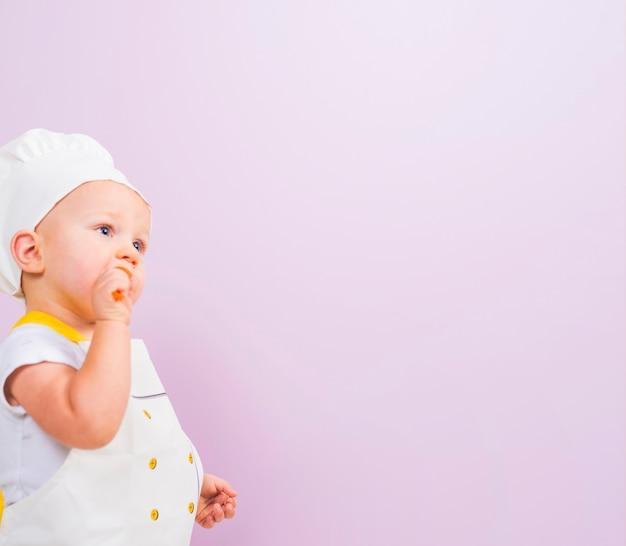 Przemyślane dziecko kucharz patrząc od hotelu
