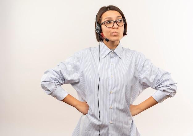 Przemyślane młoda dziewczyna call center w okularach i zestaw słuchawkowy kładąc ręce na talii patrząc na bok na białym tle na białej ścianie