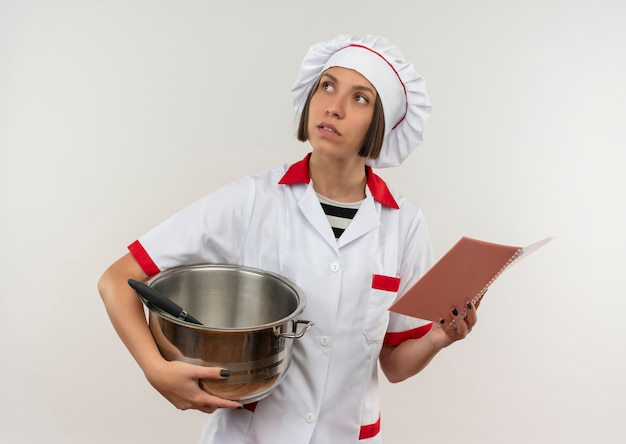 Przemyślane młoda kobieta kucharz w mundurze szefa kuchni trzymając garnek i notes patrząc w górę na białym tle na białej ścianie