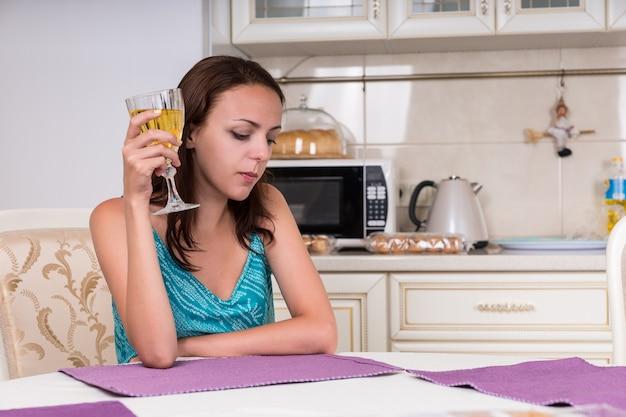 Przemyślane młoda kobieta siedzi przy stole w kuchni przy lampce wina.