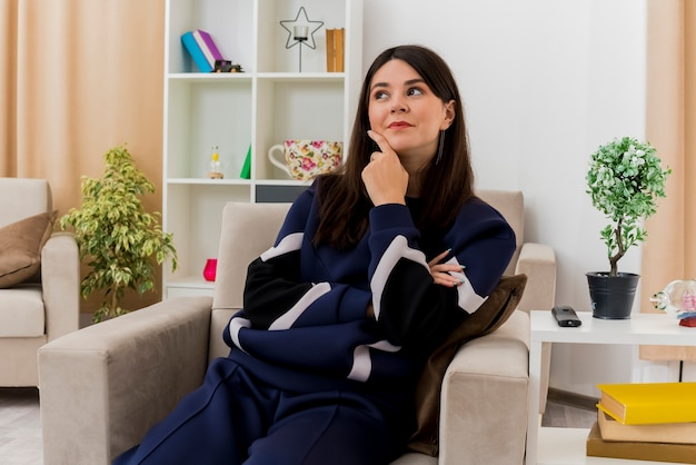 Przemyślane młode ładne kaukaski kobieta siedzi na fotelu w zaprojektowanym salonie, patrząc na bok dotykając brody