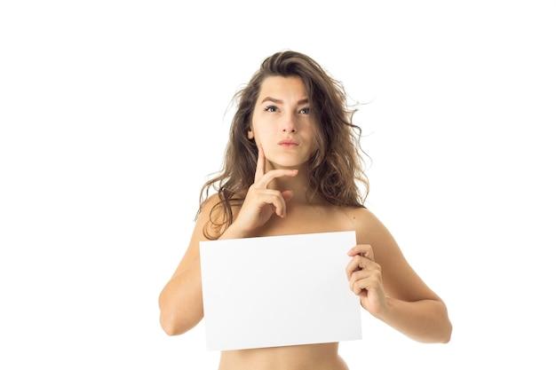 Przemyślane nagie brunetki kobiety z tabliczką na białym tle na białej ścianie