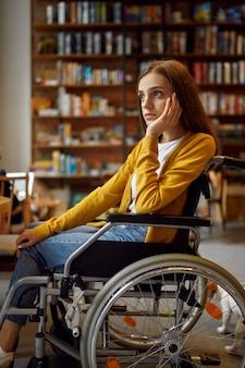 Przemyślane niepełnosprawna studentka na wózku inwalidzkim, niepełnosprawność, regał i wnętrze biblioteki uniwersyteckiej na tle. niepełnosprawna młoda kobieta studiująca na studiach, sparaliżowani ludzie zdobywają wiedzę