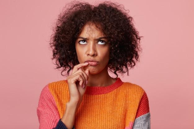 Przemyślane rozważanie liczenia skoncentrowanej kobiety afroamerykanki z fryzurą afro stojącej trzymając się za rękę w pobliżu brody patrząc w górę podwinięte oczy, odizolowane