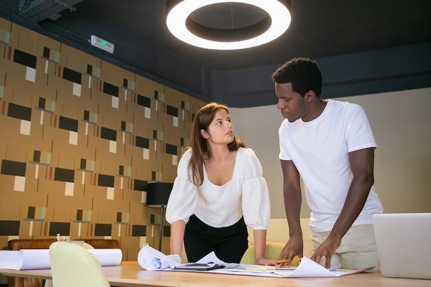 Przemyślani projektanci stoją w pomieszczeniach i obserwują się nawzajem