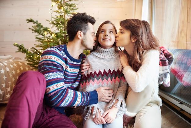 Przemyślani rodzice całują córkę