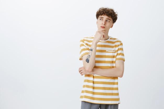 Przemyślany atrakcyjny nastoletni facet pozuje na białej ścianie