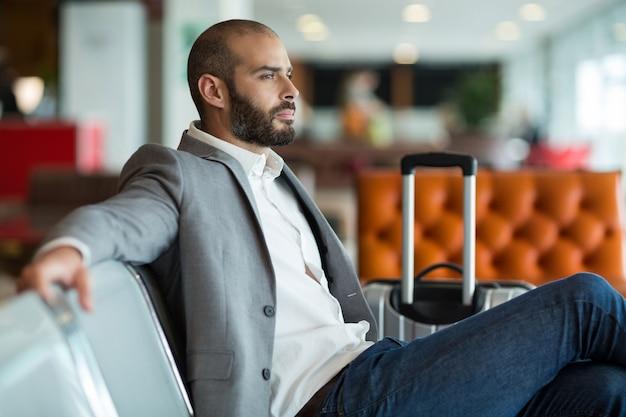 Przemyślany biznesmen siedzi na krześle w poczekalni
