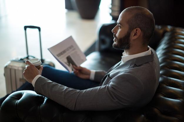 Przemyślany biznesmen trzymając gazetę i filiżankę kawy w poczekalni