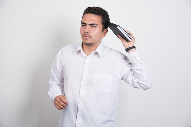Przemyślany biznesmen z notebooka stojącego na białym tle.