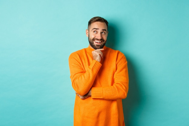 Przemyślany brodacz dokonuje wyboru, robi zakupy i patrzy w lewy górny róg, uśmiechnięty zadowolony, stoi nad turkusową ścianą.