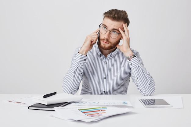 Przemyślany brodaty modny mężczyzna pracuje w biurze, otoczony grafiką i nowoczesnymi urządzeniami