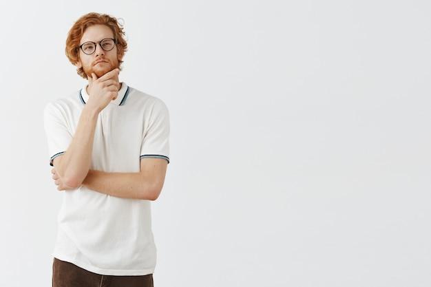 Przemyślany brodaty rudy facet pozuje na białej ścianie w okularach