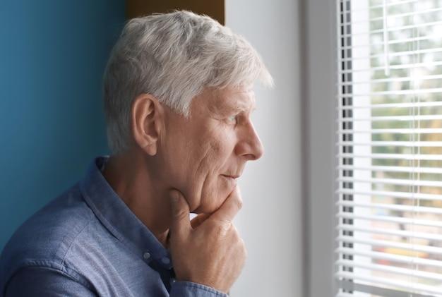 Przemyślany dojrzały mężczyzna w pobliżu okna w pomieszczeniu