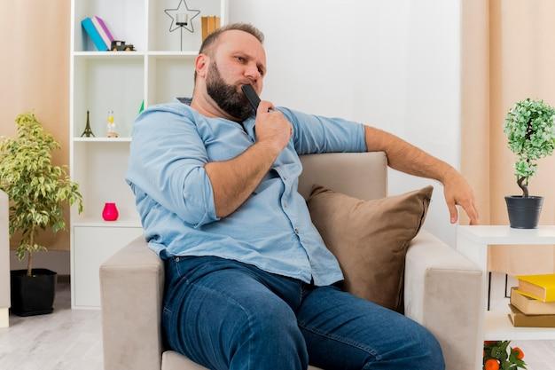 Przemyślany dorosły słowiański mężczyzna siedzi na fotelu, wkładając do ust pilota do telewizora w salonie