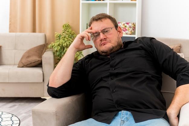 Przemyślany dorosły słowiański mężczyzna w okularach optycznych siedzi na fotelu, kładąc dłoń na głowie wewnątrz salonu