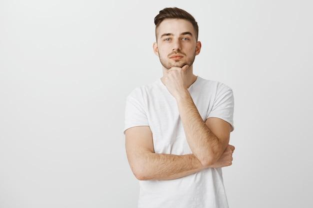Przemyślany facet szuka, myśli lub dokonuje wyboru, co kupić