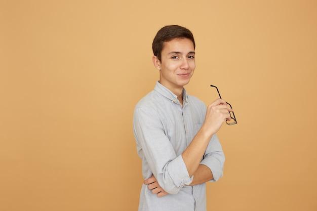 Przemyślany facet ubrany w błękitną koszulę stoi z okularami w ręku na beżowym tle w studio.