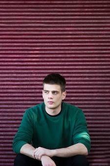 Przemyślany facet w zielonym swetrze
