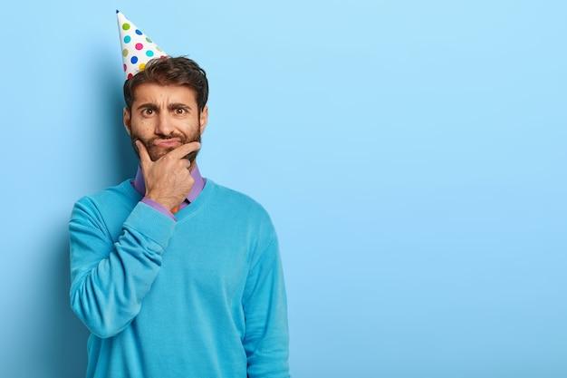 Przemyślany facet z urodzinową czapką pozuje w niebieskim swetrze
