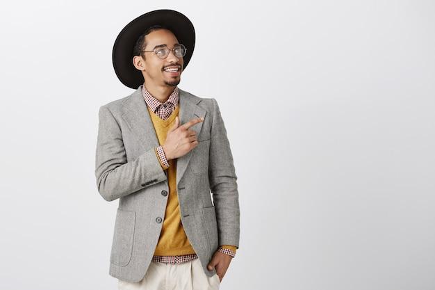Przemyślany i zainteresowany afroamerykanin w garniturze wskazuje, patrząc w prawy górny róg, wybierając produkt