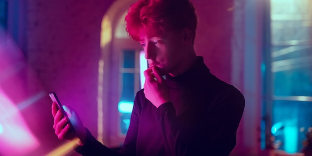 Przemyślany. kinowy portret stylowego redhair mężczyzny w oświetlonym neonami wnętrzu. stonowane jak efekty kinowe w fioletowo-różowym kolorze. kaukaski model za pomocą smartfona w kolorowych światłach w pomieszczeniu. ulotka.