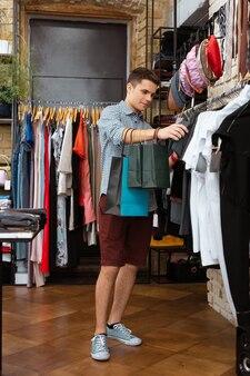 Przemyślany klient. spokojny, zrelaksowany młody człowiek trzymający papierowe torby i dotykający pięknych t-shirtów podczas samotnych zakupów