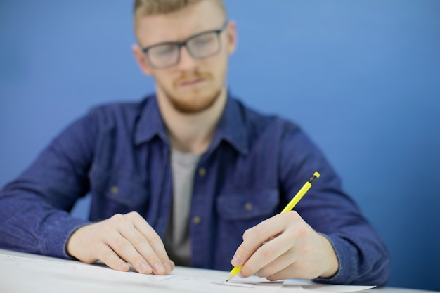 Przemyślany koncentruje się młody projektant rysuje ołówkiem na białym tle na niebieskim tle