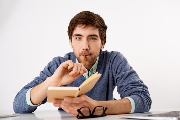 Przemyślany, kreatywny męski dziennikarz lub pisarz, gryzący ołówek, trzymający notatnik, harmonogram pisania, wyglądający na myślącego