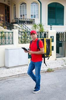 Przemyślany kurier szuka domu i trzyma tablet. profesjonalny dostawca w czerwonej czapce i koszuli z żółtą torbą termiczną z ekspresowym zamówieniem. dostawa i koncepcja zakupów online