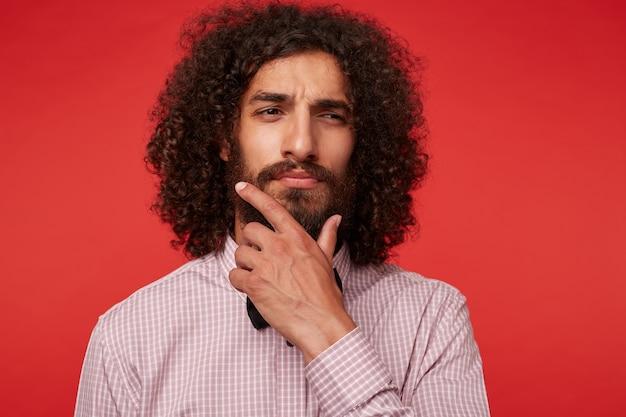 Przemyślany, ładny ciemnowłosy, kręcony facet z bujną brodą, mrużący oczy i trzymający brodę z podniesioną ręką, ubrany w formalne ubrania podczas pozowania