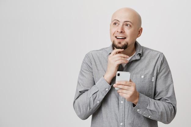 Przemyślany łysy dorosły mężczyzna myśli jak zamówić jedzenie online za pomocą aplikacji na smartfony