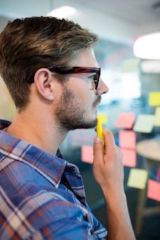 Przemyślany mężczyzna czytający notatki na szklanej ścianie w biurze