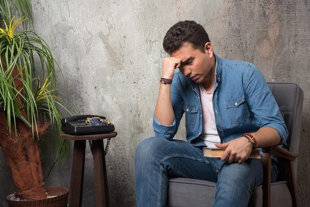 Przemyślany mężczyzna siedzi na krześle z książką na tle marmuru. wysokiej jakości zdjęcie