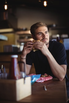 Przemyślany mężczyzna trzyma burgera