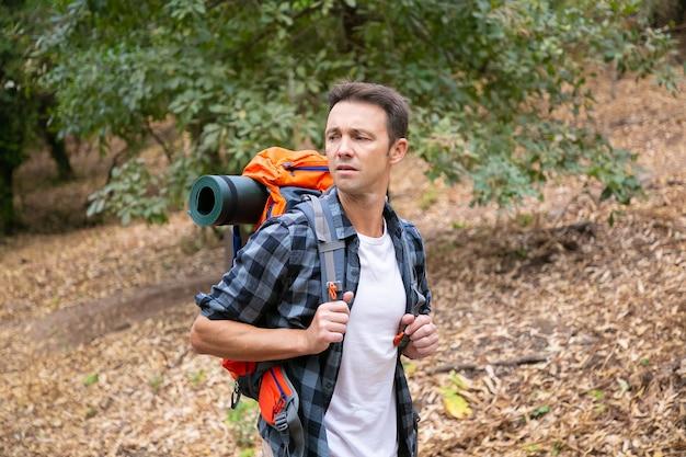 Przemyślany mężczyzna wędruje po lesie i nosi plecak. mężczyzna turysta patrząc na bok i spacery w lesie. kaukaski mężczyzna podróżnik na zewnątrz w przyrodzie. koncepcja turystyki, przygody i wakacji letnich