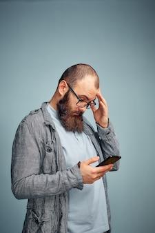 Przemyślany mężczyzna z brodą z telefonem w ręku