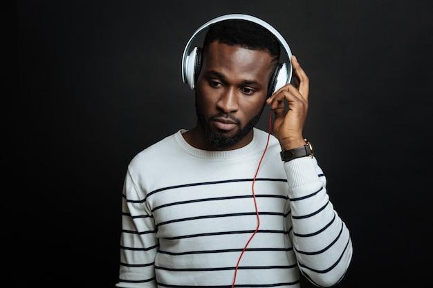 Przemyślany miły człowiek słuchający muzyki podczas korzystania ze słuchawek i stojąc odizolowany w czarnej ścianie