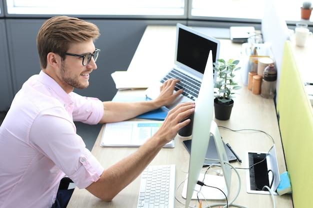 Przemyślany młody biznes człowiek w koszuli pracy przy użyciu komputera siedząc w biurze.