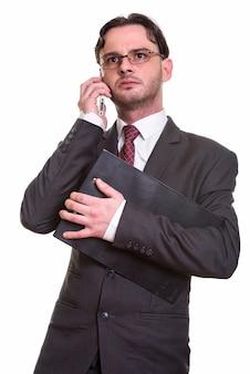 Przemyślany młody biznesmen rozmawia przez telefon komórkowy, podczas gdy holdi