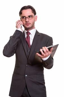 Przemyślany młody biznesmen rozmawia przez telefon komórkowy, trzymając schowek