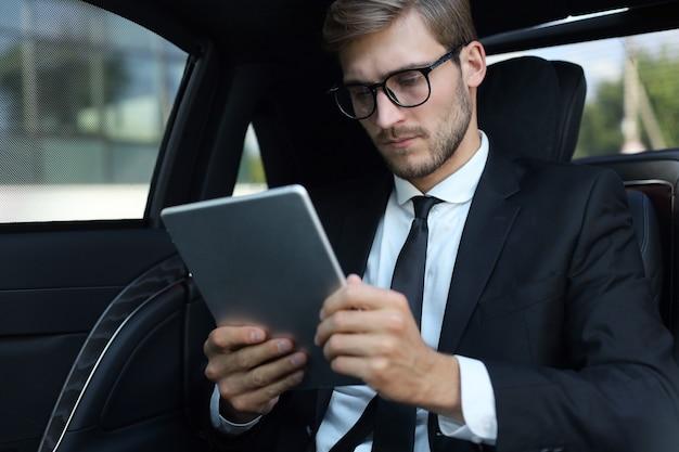 Przemyślany młody biznesmen siedzi w luksusowym samochodzie i za pomocą tabletu.