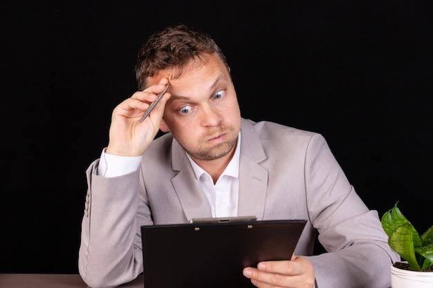 Przemyślany młody biznesmen w garniturze myśli mocno zaniepokojony rozwiązaniem problemu biznesowego