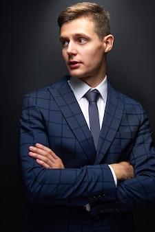 Przemyślany młody biznesmen w klasycznym czarnym garniturze