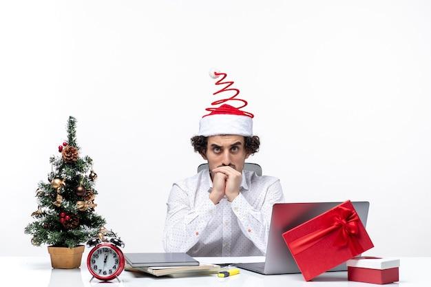 Przemyślany młody biznesmen z śmieszne czapki świętego mikołaja myśli o czymś w biurze na białym tle
