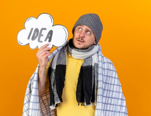 Przemyślany młody blond chory słowiański mężczyzna w czapce zimowej i szaliku owiniętym w kratę trzyma bańkę pomysłu patrząc w górę na pomarańczowej ścianie z miejscem na kopię
